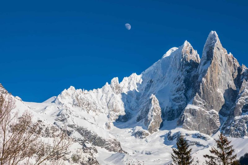 The moon against a deep blue sky above the mountains near Chamonix.  Chardonnay and and Les Drus are covered in snow.  Taken from Montroc near Argentiere in the Chamonix valley of the French Alps.